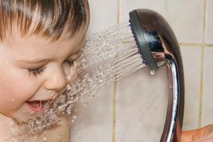 Junge spritzt sich mit Duschkopf nass